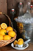 Bottles of fresh squeezed lemonade in a metal bucket filled with ice. A basket of lemons and a juice