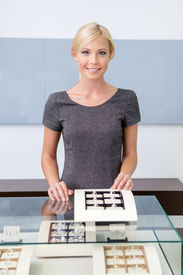 pic of jewel-case  - Shop assistant at the window case with rings at jeweler - JPG