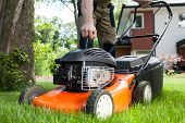 picture of dungarees  - Turning on the lawn mower by gardener
