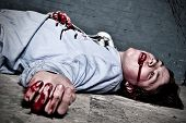 pic of murders  - Murder victim lying on the floor being shot in a basement with blood splatter on the wall - JPG