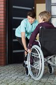 stock photo of disable  - Female caregiver helping disabled woman on wheelchair entering home - JPG