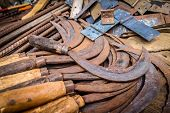 image of blunt  - Old rusted scythes for sale on the market in Madagascar - JPG