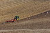 picture of four-wheel drive  - Large Modern Four Wheel Drive Tractor Ploughing with Disk Harrow in Stubble Field - JPG