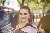 stock photo of thrift store  - smiling woman on a flea market is holding a clothes hanger.