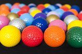 foto of miniature golf  - Assortment of colorful mini golf balls on black - JPG
