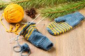 foto of pine-needle  - ball of threads knitting needles mittens and branch of pine on wooden background - JPG