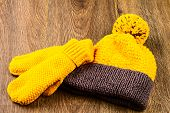 picture of knitted cap  - yellow knitting cap and mittens on wooden background - JPG
