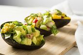 stock photo of avocado  - Avocado radish and citrus salad in avocado skins - JPG