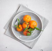 foto of clementine-orange  - Clementine tangerines with green leaves on white wooden background in a gray bowl - JPG