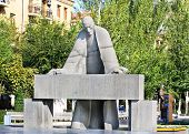 stock photo of bent over  - Sculpture of the prominent armenian architect Alexander Tamanyan bent over drawings - JPG