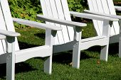 image of lawn chair  - Welcoming arrangement of three white Adirondack chairs on green - JPG