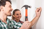 pic of hammer drill  - Young smiling couple hammer a nail a wall together - JPG