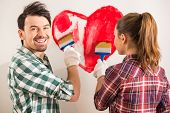 stock photo of mischief  - Young happy couple are painting a heart on the wall while doing repair at home - JPG