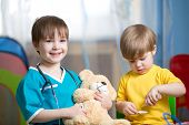 stock photo of home remedy  - kids brothers play doctor with plush toy at home - JPG