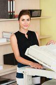 image of secretary  - Pretty young secretary using a copy machine - JPG