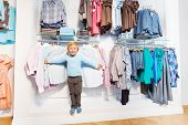 picture of clothes hanger  - Cute small boy standing among clothes on the hangers and shelf in the shop with white wall as background - JPG