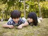 pic of playmates  - little asian boy and girl using magnifier to study grass and leaves in a park - JPG
