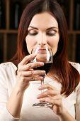 stock photo of wine cellar  - Young woman tasting wine in cellar - JPG