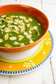 stock photo of ceramic bowl  - Swiss chard and potato cream soup with chopped roasted almonds in brown ceramic bowl - JPG