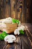 image of champignons  - Champignons with parsley in a basket on a wooden table - JPG