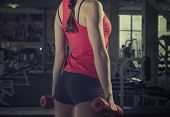 image of bum  - Young beautiful sports girl does exercises with dumbbells in the hands of the gym - JPG