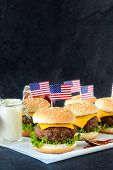 picture of beef-burger  - American mini beef burgers with cheese and USA flagsselective focus and blank space - JPG