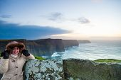 picture of cliffs moher  - Woman tourist on cliffs of Moher at sunset in Co - JPG