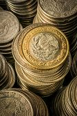 stock photo of golden coin  - A golden coin with an eagle over stacks of silver coins business wealth and success concept - JPG