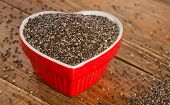 foto of seed  - chia seeds in a heart shaped bowl on rustic wooden table - JPG