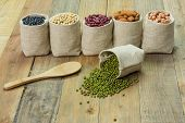 image of mung beans  - Different kinds of beans in sacks bag focus on scattered mung beans - JPG