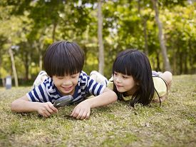 pic of japan girl  - little asian boy and girl using magnifier to study grass and leaves in a park - JPG