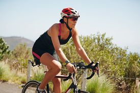 stock photo of triathlon  - Young woman triathlon athlete cycling on country road - JPG