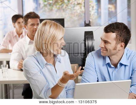 Постер, плакат: Молодые бизнесмены сидя на столе используя компьютер говорить на бизнес семинар улыбаясь , холст на подрамнике