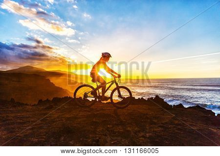 Mountain biking MTB cyclist woman cycling on bike trail on coast at sunset. Person on bike by sea in