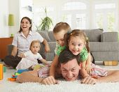 stock photo of family fun  - Happy family having fun on floor of in living room at home - JPG