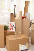 Pile of boxes in new house, champagne to celebrate moving to new home.