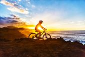 Mountain biking MTB cyclist woman cycling on bike trail on coast at sunset. Person on bike by sea in poster