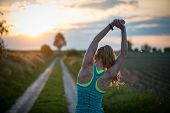 Happy successful sportswoman raising arms to the sky on golden back lighting sunset summer. Fitness  poster