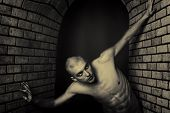 stock photo of skinheads  - Portrait of a muscular man posing in a closed space over black background and brick wall - JPG