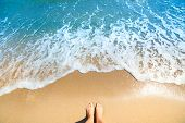 Sea foam, waves and naked feet on a sand beach. Holidays, relax, summer background poster