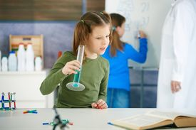picture of student teacher  - Elementary age school girl looking at test tube in science class at primary school - JPG