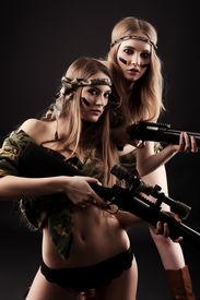 foto of girls guns  - Two sexy women in military uniform posing against black background - JPG