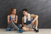 Fit Couple In Modern Gym Listening To Music On Smartphone. Sporty Man And Woman Having Rest After In poster