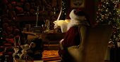 Wide Shot Of Santa Claus In Full Christmas Regalia - Including Cap - Sitting In His Workshop, Lookin poster