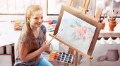 Artist painting on easel and palette in studio. Authentic happy girl child paints drawing of spring  poster