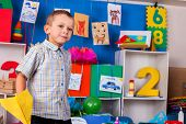Dreams flight of child in kindergarten. Happy boy child playing with origami airplane in kindergarte poster