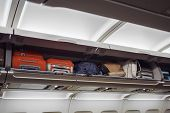 Luggage Shelf With Luggage In An Airplane. Aircraft Interior. Travel Concept. poster