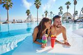 Young tourist couple on infinity pool drinking cocktails at resort on the beach poster