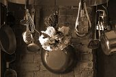picture of kitchen utensils  - sepia toned image of country kitchen with roses hanging from the pot rack drying - JPG