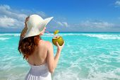 beach hat profile girl drinking a coconut fresh cocktail in tropical Caribbean sea
